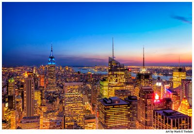 Golden city lights of the Manhattan Skyline Against dusk blue skies - Print by Mark Tisdale